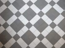 4 pilkų plytelių ir 1 pilkos plytelės kvadratais baltų keramikinių plytelių fone danga