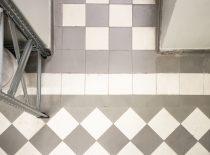 baltų ir pilkų keramikinių plytelių, suklotų šachmatine tvarka su lenkta grindjuoste danga