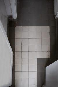 baltų keramikinių plytelių su pilku apvadu ir lenkta grindjuoste danga